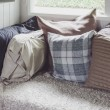 Many of pillows on sofa with blanket in living room at home — Stock Photo #67730719