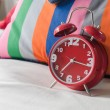 Red alarm clock on bed — Stock Photo #67736195