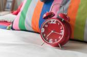 Red alarm clock on bed  — Stock Photo