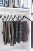 Pants hanging on rack in wardrobe — Stock Photo