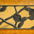 Close up curved steel beautiful rose on yellow park bench. — Stock Photo #65850923