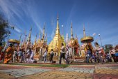 Buddhist people praying and walking around a golden pagoda. — Stock Photo