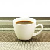 Espresso in white cup on tablemat — Stock Photo