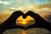 Hands make heart at sunset — Stock Photo