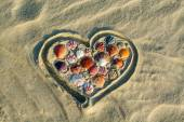 Heart made of sea shells lying on sand — Stock Photo
