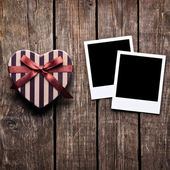 Heart shaped box and two blank photo frames — Stock Photo