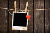 Photo frame with paper heart hang on rope — Stockfoto