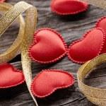 Small hearts with gold ribbon — Stock Photo #63052477