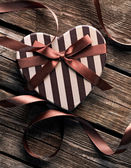 Gift box with curved ribbon on old wood — Stockfoto