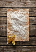 Crumpled paper with gold bow — Stock Photo