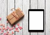 Gift box with gift tag, hearts and tablet computer — Stock Photo