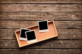 Instant photo frames on wooden box — Stock Photo