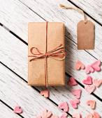 Caja de regalo con etiqueta de regalo en blanco y montón de corazones — Foto de Stock
