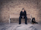 Young man sitting on a bench with your best four-legged friend — Stock Photo