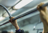 People holding handrail in the metro hand in focus — Stockfoto