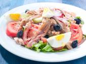 Nicoise salad with egg , anchovies , onions , lettuce and tuna — Stock Photo