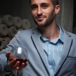 Young man stands with glass of wine — Stock Photo #62383707
