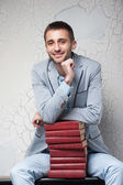Young man sits with books — Stock Photo