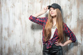 Pretty hipster woman with hat is standing near the wall — Stock Photo