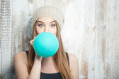 Pretty hipster woman is inflating colored balloon — Stock Photo