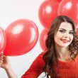 Pretty young woman in red dress is giving present — Stock Photo #77121807