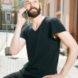 Handsome young man with beard in city — Stock Photo #77705120