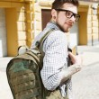 Attractive young hipster guy is walking across city — Stock Photo #77705652