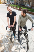 Attractive young hipster guys are cycling in city — Stock Photo