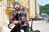 Cheerful young man is cycling in city — Стоковое фото