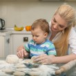 Pretty young housewife is cooking with her child — Stock Photo #78241350