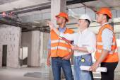 Cheerful builders are working on plan of building — Stock Photo