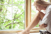 Beautiful young woman is resting near a window — Stock Photo