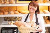 Cheerful senior baker is selling baked products — Stock Photo