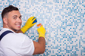 Attractive young cleaner is washing wall with a wisp — Stock Photo