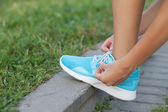 Young woman is fixing laces of her running shoes — Stock Photo