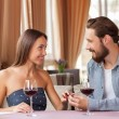 Attractive young loving couple is celebrating in restaurant — Stock Photo #83518968