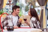 Pretty loving couple is relaxing with water pipe in cafe — Stockfoto