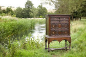 Chest of drawers on stand outdoors by a river — Stock Photo