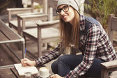 Woman in checkered shirt and hat studying outdoors — Stock Photo