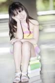 Girl sitting on books — Stock Photo