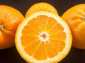 Group of oranges and half orange on black — Stock Photo