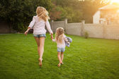 Back view of mother and daughter running in the garden — Stock Photo