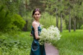 The girl in the dress gathers flowers — Stock Photo