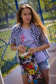 Cute girl in shorts with a skateboard on the Playground — Stock Photo