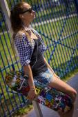 Cute girl in shorts with a skateboard on the Playground — Стоковое фото