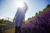 Girl stands near the meadows with flowers — Stock Photo