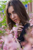 Portrait of young beautiful girl in flowers — Stock Photo