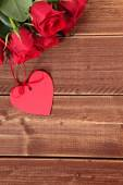 Valentine background of gift tag and red roses on wood. Space fo — ストック写真