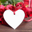 Valentine background of  white gift tag and red roses on wood. S — Stock Photo #63949521