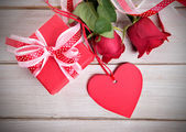 Valentine background of gift box, two red roses and red gift tag — Fotografia Stock